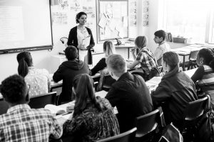 A teacher at the front of their class teaching a group of secondary school students