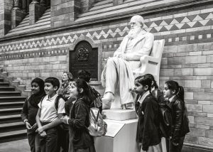 Schoolchildren on a school trip, posing for a photograph in front of the Charles Darwin statue, at the Natural History Museum, London, England, UK.