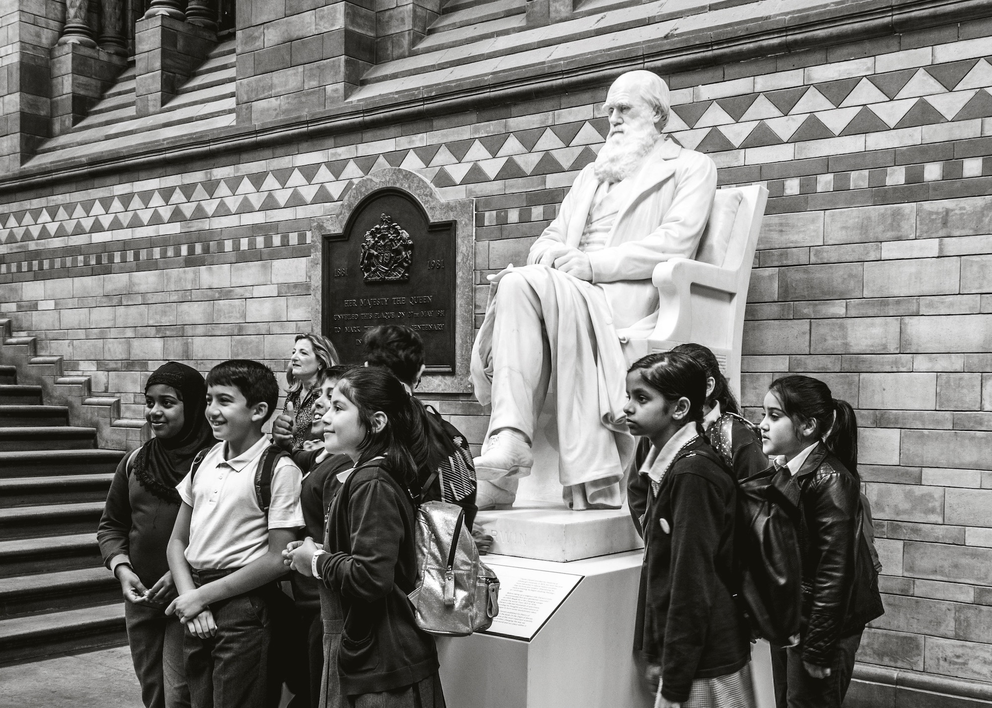 KD6X1J Schoolchildren on a school trip, posing for a photograph in front of the Charles Darwin statue, at the Natural History Museum, London, England, UK.