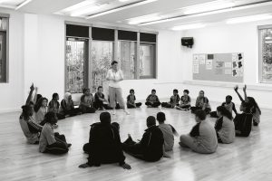 A group of secondary school students are sat in a circle on the floor with legs crossed, a few of them have their hands up. Their teacher is standing in the middle of the circle.