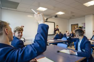 A secondary school classroom, a student has raised their hand to answer a question.