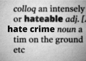 An excerpt from the dictionary with the words 'hate crime' in bold and all other words blurred out.