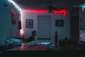 A teenager sitting in a dark room playing video games