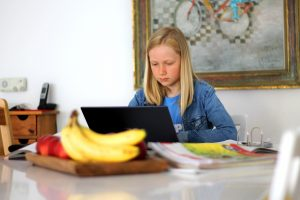 A child sits at a desk looking at a laptop