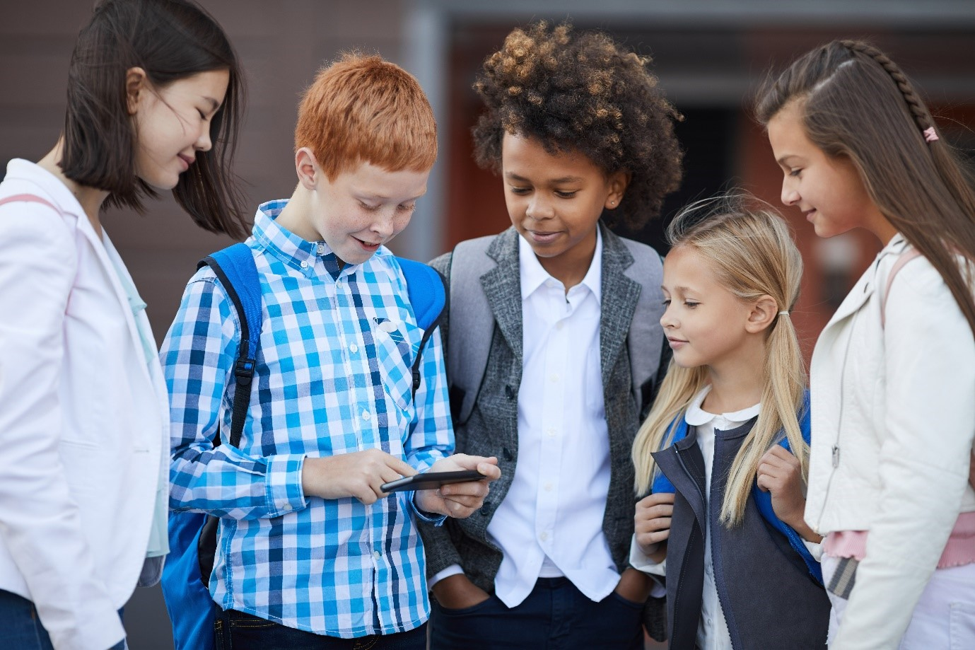 A group of four children crowd round a child with a mobile phone and look at the screen