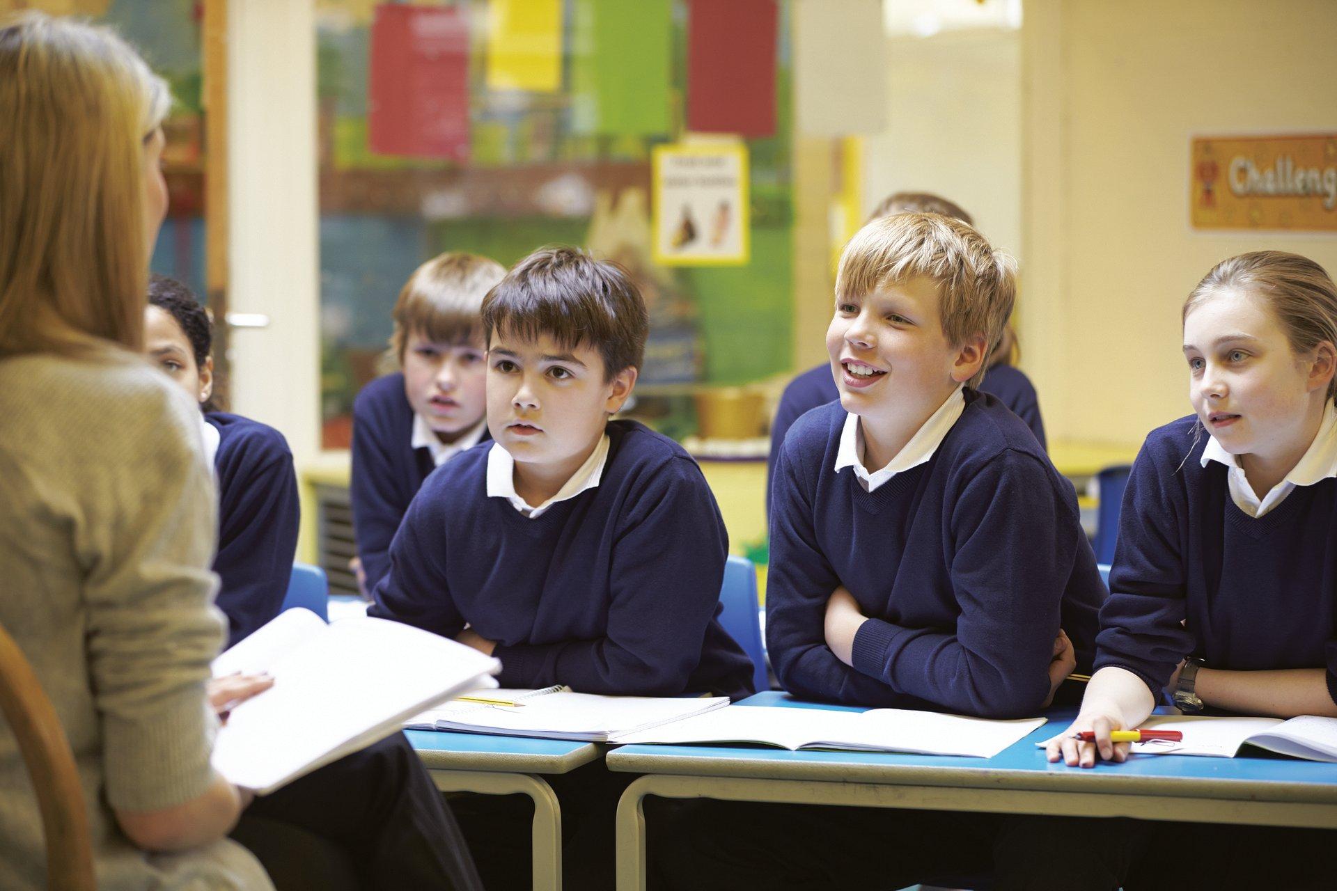 School children in a classroom listening to their teacher read a book